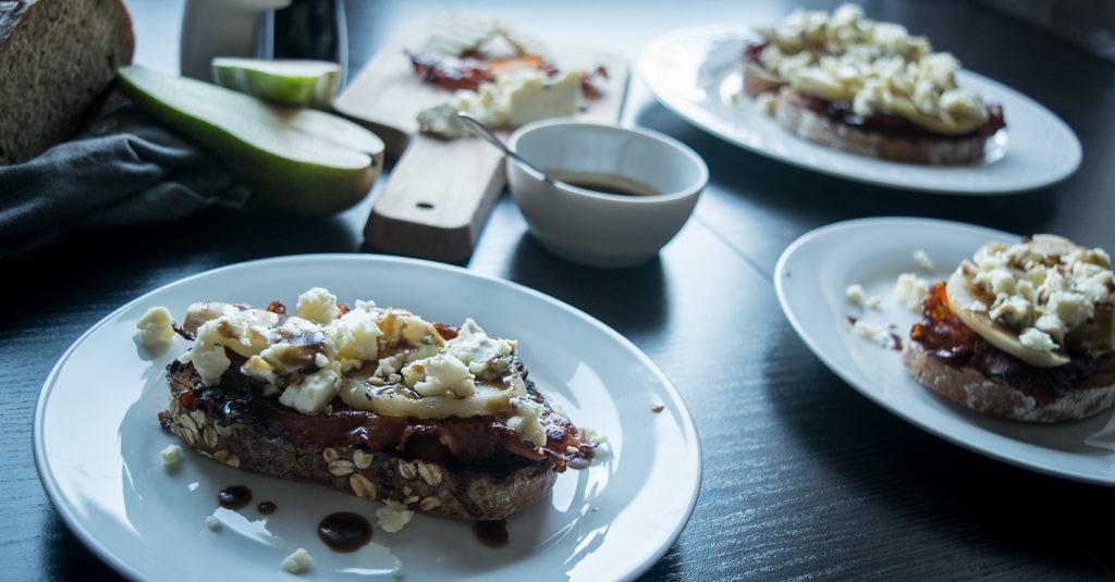 grzanki z boczkiem grillowaną gruszka i serem pleśniowym na stole na talerzach