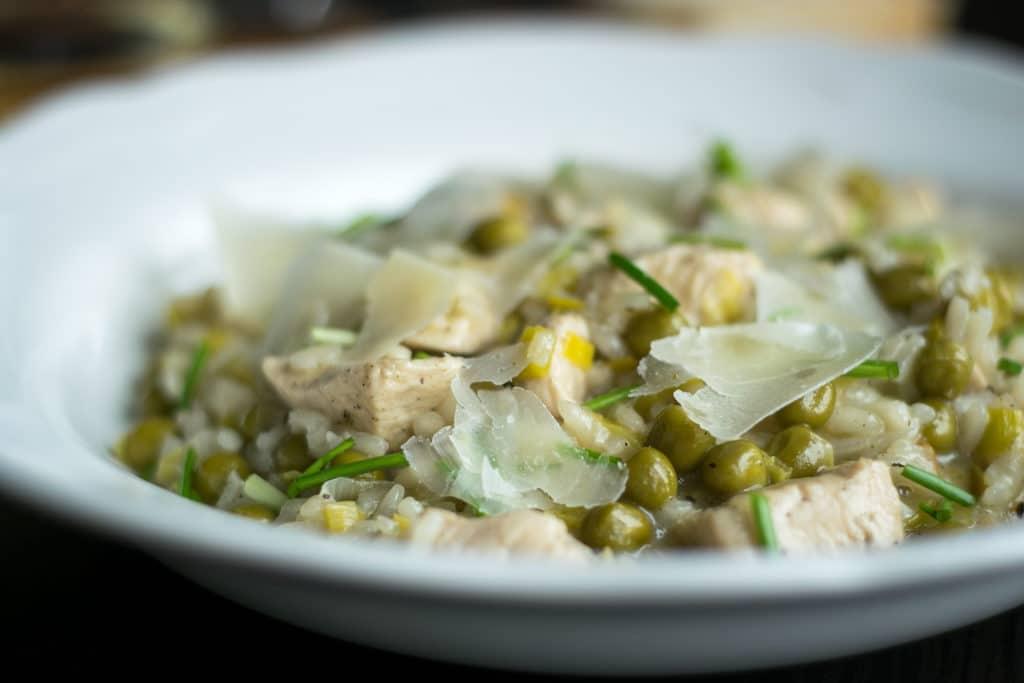 risotto z kurczakiem, porem i groszkiem na talerzu